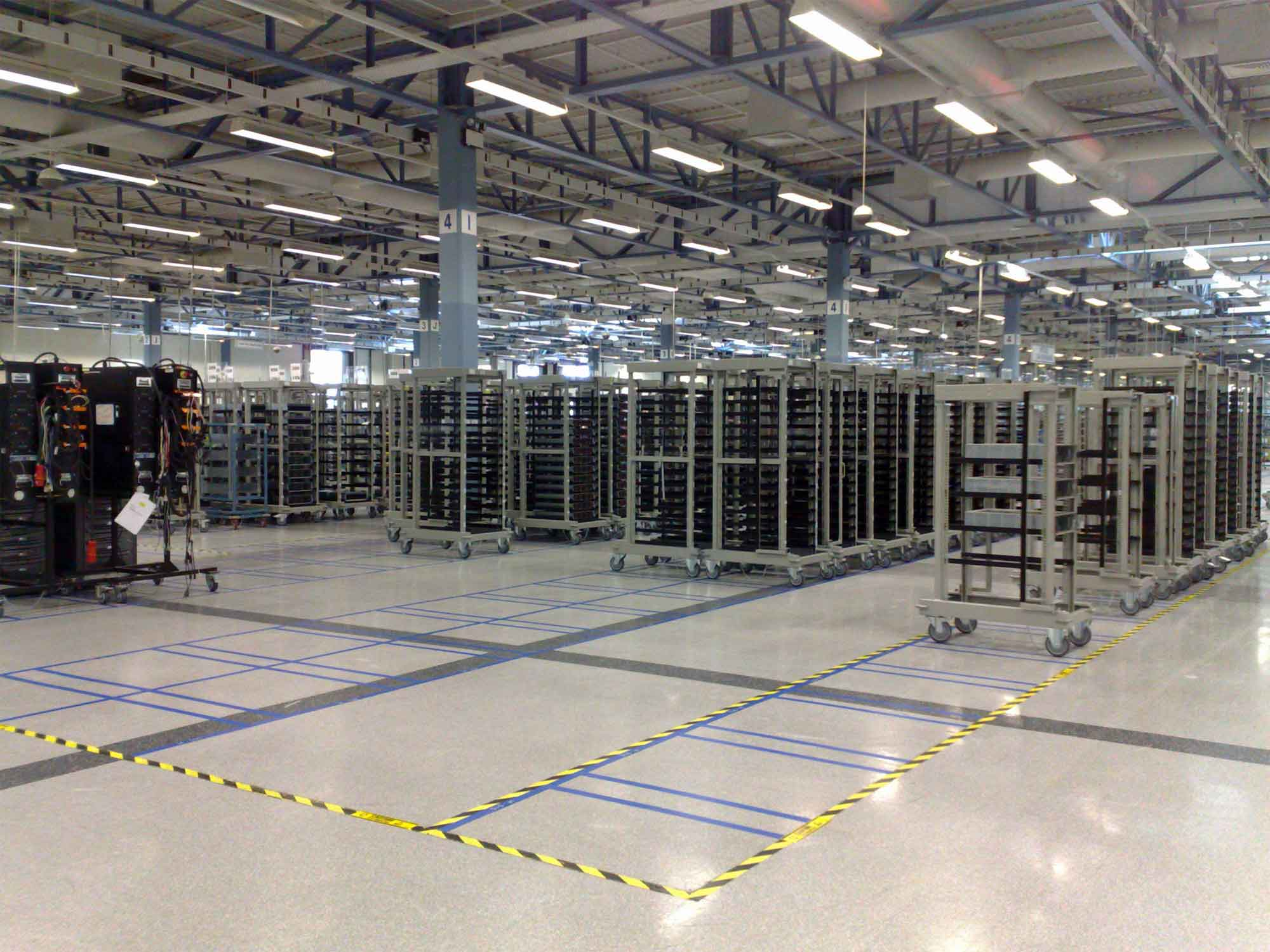Photograph showing server trolleys in a large warehouse with marked location positions
